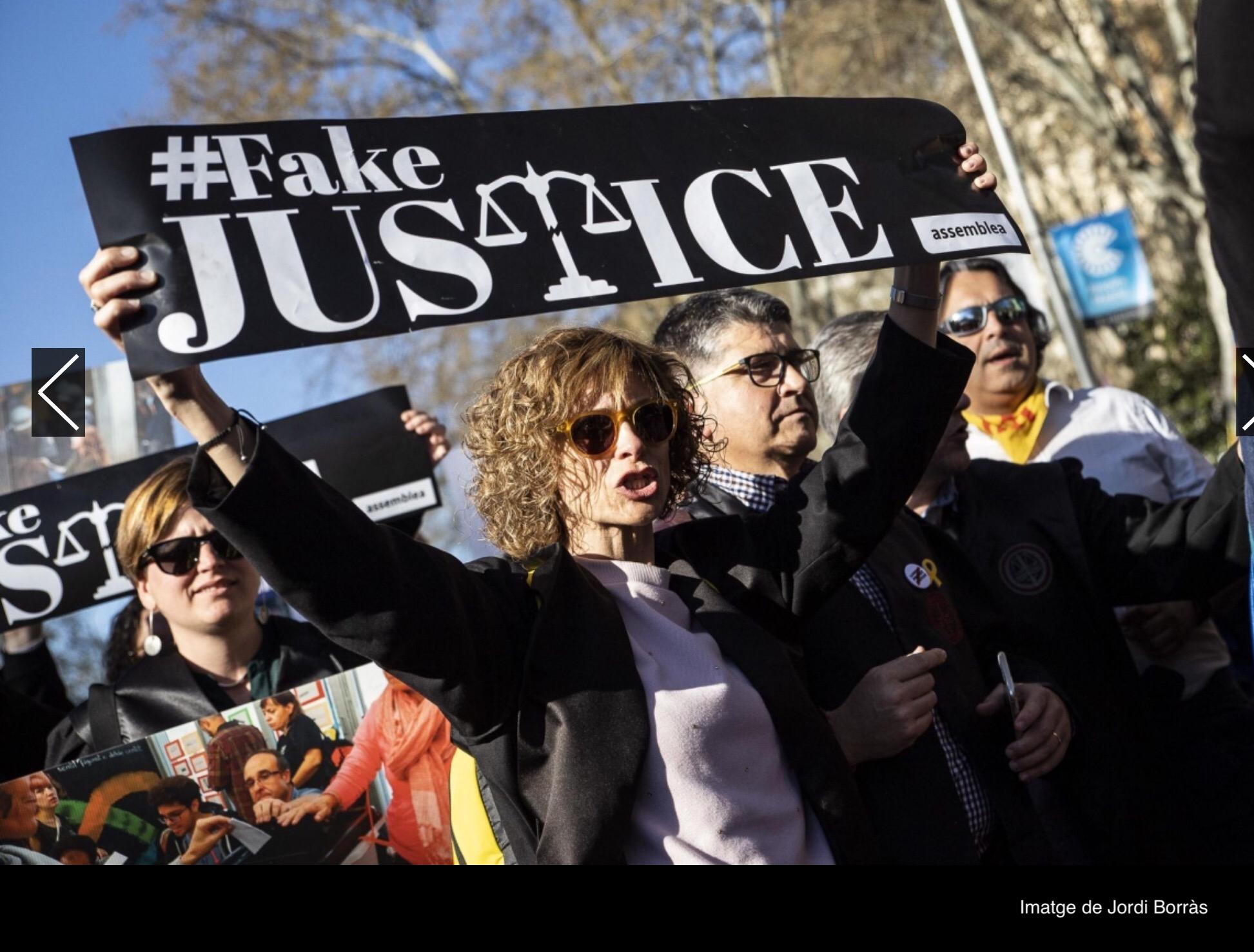 Manifestant amb pancarta de #FakeJustice dirigida a la justícia espanyola